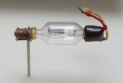 Hậu duệ của bóng đèn sợi đốt: Các ống chân không là một biến thể của các bóng đèn sợi đốt thông thường, được phát triển dựa trên nghiên cứu của Thomas Edison về khả năng phát electron của các dây tóc bóng đèn. Chẳng hạn như ống Audion thế hệ đầu, chế tạo năm 1906, trong hình trên trông rất giống một cái bóng đèn cho dù ta không thấy dây tóc đâu do nó đã bị cháy từ lâu. Sợi dây tóc đó, trước đây, đóng vai trò như một cực âm (cathode) mà từ đó các electron bay tới cực dương (anode) là một tấm kim loại nằm ở chính giữa của bóng thủy tinh. Dòng điện từ cực âm tới cực dương có thể được điều khiển bằng cách thay đổi điện áp trên lưới, là sợi dây dẫn chạy zigzag ở dưới tấm cực dương. Hình: Gregory Maxwell.